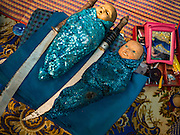 """30 JANUARY 2016 - NONTHABURI, NONTHABURI, THAILAND:  Props, including traditional Thai swords and dolls (that represent babies) at  a """"likay"""" show at Wat Bua Khwan in Nonthaburi, north of Bangkok. Likay is a form of popular folk theatre that includes exposition, singing and dancing in Thailand. It uses a combination of extravagant costumes and minimally equipped stages. Intentionally vague storylines means performances rely on actors' skills of improvisation. Like better the known Chinese Opera, which it resembles, Likay is performed mostly at temple fairs and privately sponsored events, especially in rural areas. Likay operas are televised and there is a market for bootleg likay videos and live performance of likay is becoming more rare.    PHOTO BY JACK KURTZ"""