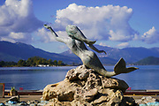 Mermaid statue and water fountain on the waterfront of Poros Town, Greece. Poros is a small Greek island-pair in the southern part of the Saronic Gulf, Greece