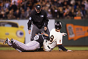 San Francisco Giants first baseman Brandon Belt (9) is tagged at second base by Colorado Rockies shortstop Cristhian Adames (18) at AT&T Park in San Francisco, Calif., on September 27, 2016. (Stan Olszewski/Special to S.F. Examiner)