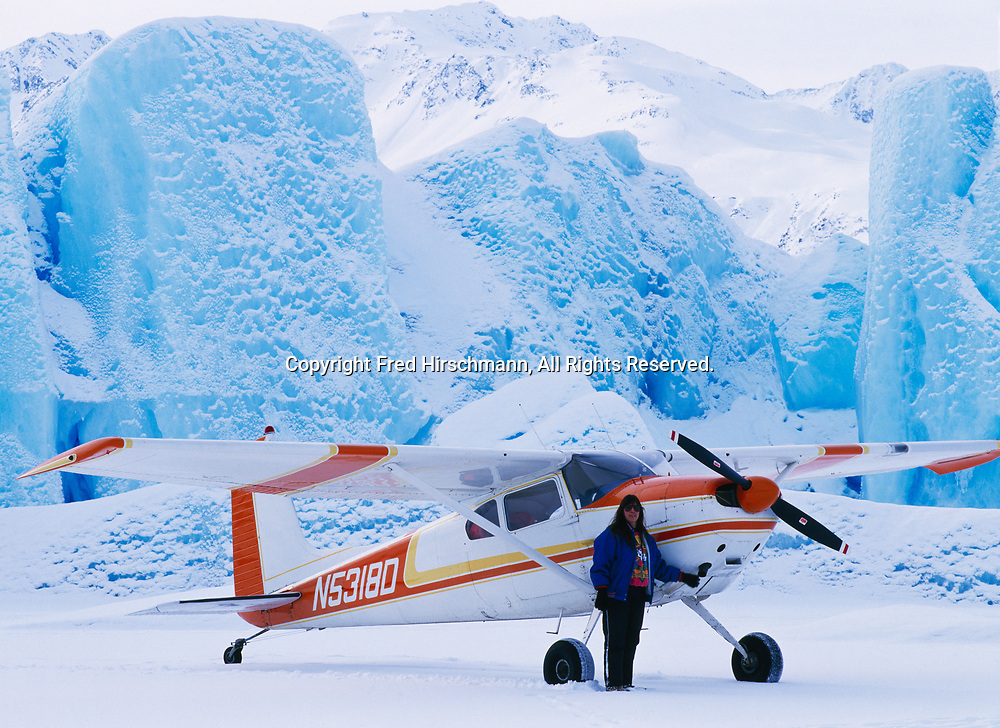 Bush Pilot Ellen Paneok with Gary King's Cessna 180 parked on ice of Inner Lake George, icebergs from Colony Glacier, Alaska.