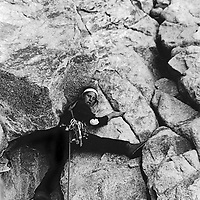 Roger Schley struggles with a difficult climbing move on the east face of 14,153' Mount Sill above the Palisade Glacier of the Sierra Nevada.