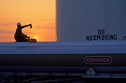 silhouette of a man working on a rig at sunset