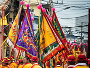 """23 JUNE 2015 - MAHACHAI, SAMUT SAKHON, THAILAND:  Prayer flags are carried through Mahachai during the City Pillar Shrine procession in Mahachai. The Chaopho Lak Mueang Procession (City Pillar Shrine Procession) is a religious festival that takes place in June in front of city hall in Mahachai. The """"Chaopho Lak Mueang"""" is  placed on a fishing boat and taken across the Tha Chin River from Talat Maha Chai to Tha Chalom in the area of Wat Suwannaram and then paraded through the community before returning to the temple in Mahachai.  PHOTO BY JACK KURTZ"""