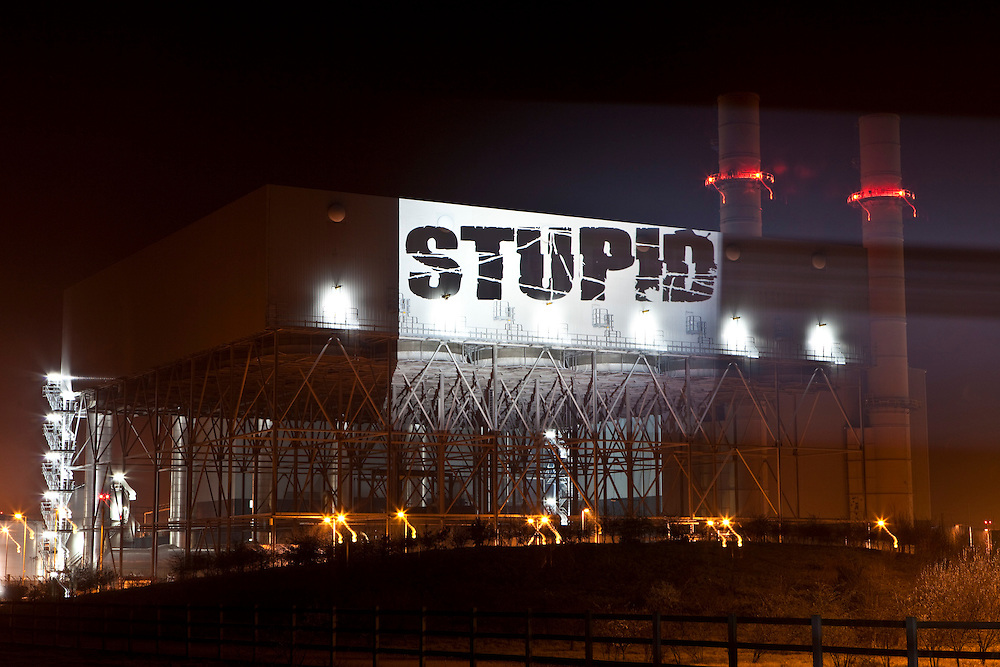 The word 'STUPID' is projected onto the side of Kingsnorth power station, Kent, UK.