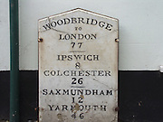 Old milestone showing distances to London, Ipswich, Colchester, Saxmundham, and Yarmouth in the town of Woodbridge, Suffolk, England, UK