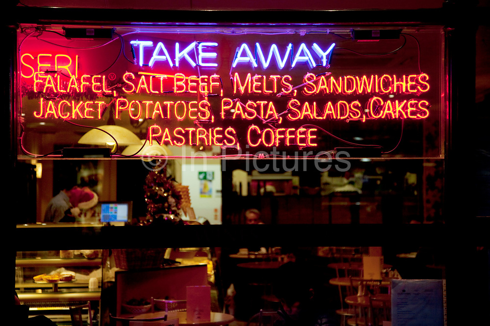 Neon take away sign offering falafel, salt beef, sandwiches, coffee, pastries etc.