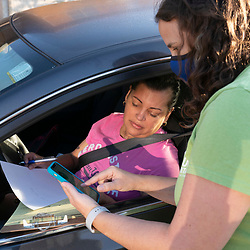 Catholic Charities worker Karen Green (r) helps Austinite Irma Flores with her voter registration application during a four-hour drive October 1, 2020 in Austin.  Several dozen mostly Hispanic U.S. residents were signed up in the non-partisan effort.
