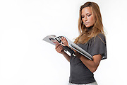young woman in her 20s reads a fashion magazine on white background Model release available