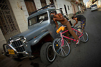 Cuban Bicyclist in looks into mirror of off-road vehicle