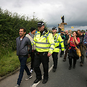 Anti-fracking  activists and protesters outside the gates of Quadrilla's fracking site June 31st, Lancashire, United Kingdom. An activist is arrested for jumping on a truck bringing equipment after he handed himself over. The struggle against fracking in Lancashire has been going on for years. The fracking company Quadrilla is finally ready to bring in a drill tower to start drilling and anti-frackinhg activists are waiting in front of the gates to block the equipment getting in. Fracking is a destructive and potential dangerous and highly contentious method of extracting gas and this site will be the first of many in the United Kingdom reaching miles out under ground.