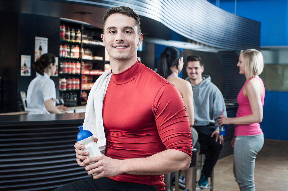 Smiling young man at the bar of a gym