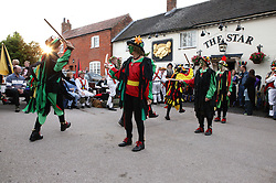 Group of Morris dancers performing dance outside village pub,