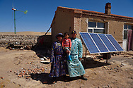 Mongolian Shepherd Manduhu, left, with his brother in law and his sisters son, in front of his house, wind mill and solar panels, Inner Mongolia, China