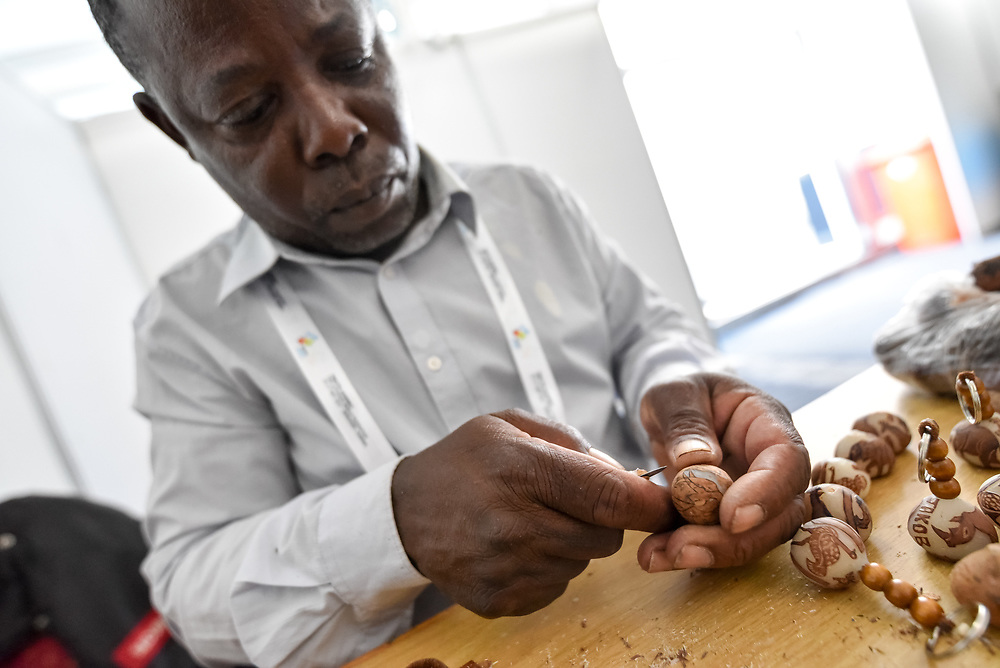 """11 May 2017, Windhoek, Namibia: Erwin Eichab carves Makalani necklaces from the fruits of a palm tree, in the Omatala, an open space at the Lutheran World Federation's Twelfth Assembly, for exhibitions, workshops, and informal encounters. The Twelfth Assembly of the Lutheran World Federation gathers in Windhoek, Namibia, on 10-16 May 2017, under the theme """"Liberated by God's Grace"""", bringing together some 800 delegates and participants from 145 member churches in 98 countries."""