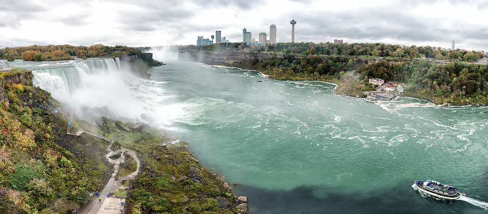 High resolution panorama of the American Falls at Niagara Falls on the Niagara River on the border between the United States and Canada. In the distance at left of frame can be seen part of the larger Horseshoe Falls. The Maid of the Mist, carrying tourists, is at bottom right.
