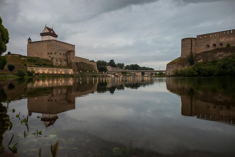 Narva, Estonia - July 23, 2015: The Narva River separates the cities of Narva, Estonia (left) and Ivangorod, Russia (right). The tower on the left is part of Herman Castle, first built by the Danes in the 13th century. The castle in Russia, on the right, was built by Ivan III of Muscovy in 1492.
