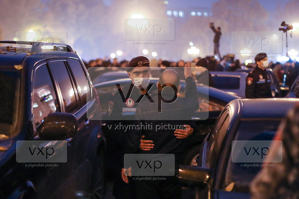 A policeman holds a man shouting at the protestors while they were marching outside Government building demanding the resignation of Armenia's Prime Minister Nikol Pashinyan marches outside PM's office in Yerevan, Armenia on Tuesday, Dec 15, 2020. Capital Yerevan has seen on-going protests since the November 9 ceasefire that was signed in Nagorno-Karabakh between Armenia, Russia, and Azerbaijan, an agreement that came into effect and resulted with Armenian troops withdrawal from the troubled region. (VXP Photo/ Vudi Xhymshiti)