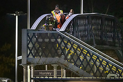 © Licensed to London News Pictures. 04/01/2019. Horsley, UK. Police and mortuary workers carry a body across the footbridge at Horsley Railway station in Surrey where a man has been stabbed to death on a train. A murder investigation has been launched after the man was attacked while on board the 12. 58pm train service travelling between Guildford and London Waterloo. . Photo credit: Peter Macdiarmid/LNP