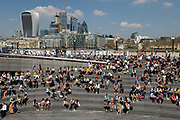 Crowds of office workers and tourists at lunchtime sit in the Scoop on the South Bank seen in front of City of London skyscrapers during hot and sunny weather on April 20, 2018 in London, England. Yesterday the United Kingdom experienced the hottest day in April since 1949, with temperatures reaching 27.9C 82.2F in London.