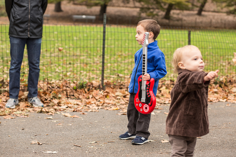 A boy with a toy guitar is transfixed by Doug Wamble.