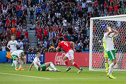 PARIS, FRANCE - Saturday, June 25, 2016: Northern Ireland's Gareth McAuley looks dejected after scoring an own goal during the Round of 16 UEFA Euro 2016 Championship match against Wales at the Parc des Princes. (Pic by Paul Greenwood/Propaganda)
