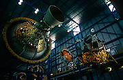 Suspended above the heads of space tourists are an Apollo rocket stage for the Saturn V rocket and a Lunar Module.