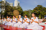 20 OCTOBER 2012 - BANGKOK, THAILAND: Women lead a prayer for peace in southern Thailand during a special alms giving ceremony in Bangkok. More than 2,600 Buddhist Monks from across Bangkok and thousands of devout Thai Buddhists attended the mass alms giving ceremony in Benjasiri Park in Bangkok Saturday morning. The ceremony was to raise food and cash donations for Buddhist temples in Thailand's violence plagued southern provinces. Because of an ongoing long running insurgency by Muslim separatists many Buddhist monks in Pattani, Narathiwat and Yala, Thailand's three Muslim majority provinces, can't leave their temples without military escorts. Monks have been targeted by Muslim extremists because, in the view of the extremists, they represent the Thai state.         PHOTO BY JACK KURTZ