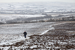***CAPTION CORRECTION***© Licensed to London News Pictures. 14/01/2015. Wheddon Cross, Somerset, UK. A woman walking on Dunkery Hill in Exmoor National Park, Somerset this morning, 14th January 2015. Snow has fallen overnight across many parts of England, causing travel disruption in some areas.  Photo credit : Rob Arnold/LNP