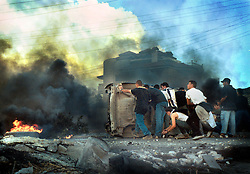 "Palestinians express their rage towards the Israeli army in the West Bank town of Ramallah,  October 11, 2000.  Guns are still rattling  as the two sides grope to find a solution to the  fighting.  Palestinian leader Yasser Arafat  says ""We have funerals everyday. Who can control a people who have funerals every day?"" (Photo by Ami Vitale)"