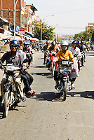 Locals navigate the hectic streets of Phnom Penh in moped convoy, Cambodia