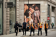 Provocative large scale Suit Supply brand advertising images depicting a mand and woman French kissing in shop windows near Regent Street on 26th May 2021 in London, United Kingdom. Passing people interact with the huge figures in these photographs as if tiny in comparison. This area of the capital is known for its exclusive shops whose vrands are aimed at the rich and wealthy.