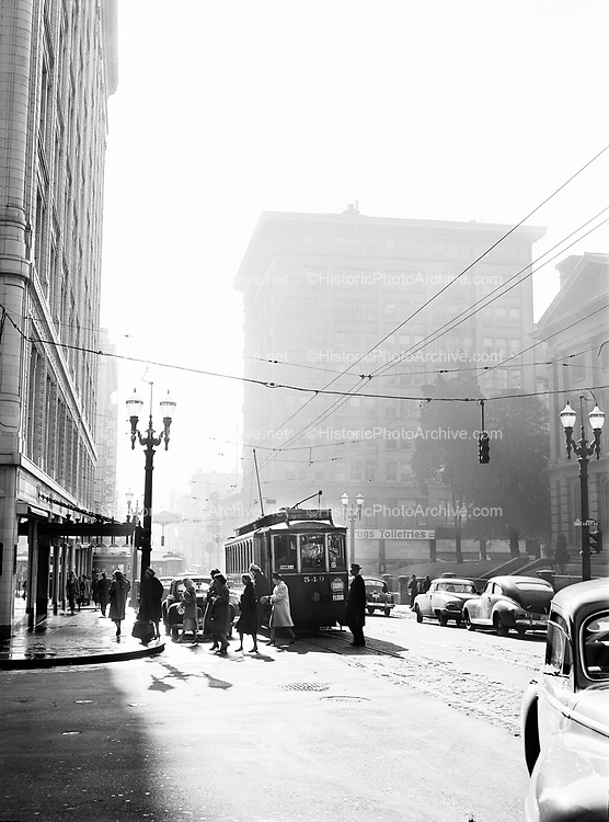 """9969-7187. Street cars and people going to work at southwest Sixth and Morrison Street, Portland, Oregon. (""""Portland Morning""""). April 8, 1948"""