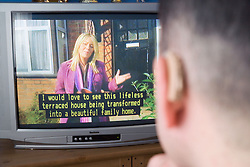 Man with a hearing impairment watching subtitles on television,