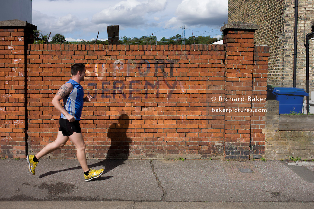 A jogger runs past some 'Support Jeremy' (Corbyn, - the left-wing Labour leader elected in September 2015) writing on a Peckham, south London brick wall.