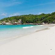 Empty white sand beach on Raya island with bungalow on the rocks, Thailand