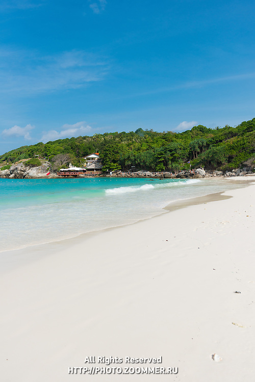 Empty white sand beach on Raya island with bungalow on the rocks, Thailand