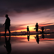 Asian tourists during sunset at White Beach,  Boracay Island, the Philippines on October 4, 2008, Photo Tim Clayton.....Asian tourists at White Beach, Boracay Island, the Philippines...The 4 km stretch of White beach on Boracay Island, the Philippines has been honoured as the best leisure destination in Asia beating popular destinations such as Bali in Indonesia and Sanya in China in a recent survey conducted by an International Travel Magazine with 2.2 million viewers taking part in the online poll...Last year, close to 600,000 visitors visited Boracay with South Korea providing 128,909 visitors followed by Japan, 35,294, USA, 13,362 and China 12,720...A popular destination for South Korean divers and honeymooners, Boracay is now attracting crowds of tourists from mainland China who are arriving in ever increasing numbers. In Asia, China has already overtaken Japan to become the largest source of outland travelers...Boracay's main attraction is 4 km of pristine powder fine white sand and the crystal clear azure water making it a popular destination for Scuba diving with nearly 20 dive centers along White beach. The stretch of shady palm trees separate the beach from the line of hotels, restaurants, bars and cafes. It's pulsating nightlife with the friendly locals make it increasingly popular with the asian tourists...The Boracay sailing boats provide endless tourist entertainment, particularly during the amazing sunsets when the silhouetted sails provide picture postcard scenes along the shoreline...Boracay Island is situated an hours flight from Manila and it's close proximity to South Korea, China, Taiwan and Japan means it is a growing destination for Asian tourists... By 2010, the island of Boracay expects to have 1,000,000 visitors.