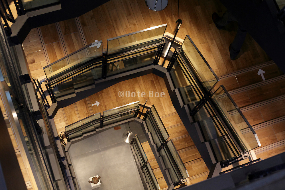 looking down a grand stairwell with direction arrows on the stairs