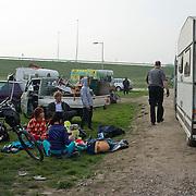Amsterdam, 02-04-2014. De politie is vanmorgen begonnen met de ontruiming van het kamp met 'stadsnomaden' op het braakliggende terrein aan Dortmuiden in Westpoort in Amsterdam.De circa vijftig bewoners bivakkeren al ongeveer drie jaar op het braakliggende terrein aan Dortmuiden in Westpoort, dat de naam 't Landje heeft meegekregen. Het staat vol met zo'n 75 caravans, campers en andere bouwsels. De circa vijftig bewoners moesten vertrekken omdat ze er volgens de gemeente illegaal een kamp hadden neergezet. Ook zouden ze overlast veroorzaken.Uit protest tegen de ontruiming stichtten de bewoners dinsdagavond brand in het kamp. De politie hield daarbij een oogje in het zeil. Voor zo ver bekend hebben zich geen grote incidenten voorgedaan.