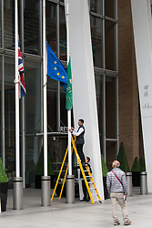 London, June 4th 2017. A worker at the Shangrila Hotel at The Shard lowers the flags to half mast during a massive policing operation in the aftermath of the terror attack on London Bridge and Borough Market on the night of June 3rd which left seven people dead and dozens injured.