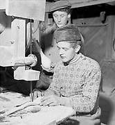 Male woodworker using saw machine, Finland 1956