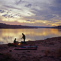 Lake Powell, Utah. Campers relax by a fire next to huge reservoir.