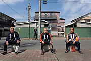 Four festival supporters in traditional happy coats rest after the Kanamara matsuri or festival of the Steel phallus Kawasaki Daishi, Kawasaki, Kanagawa, Japan. Sunday, April 2nd 2017. The Kanamara Penis festival takes place on the first Sunday of April and celebrates the local legend of a penis eating demon who was defeated after being tricked into biting a steel phallus. The festival is popular with Japan's gay community and now uses its notoriety to raise money for HIV and AIDS charities. It is also wildly popular with foreign and Japanese.tourists.