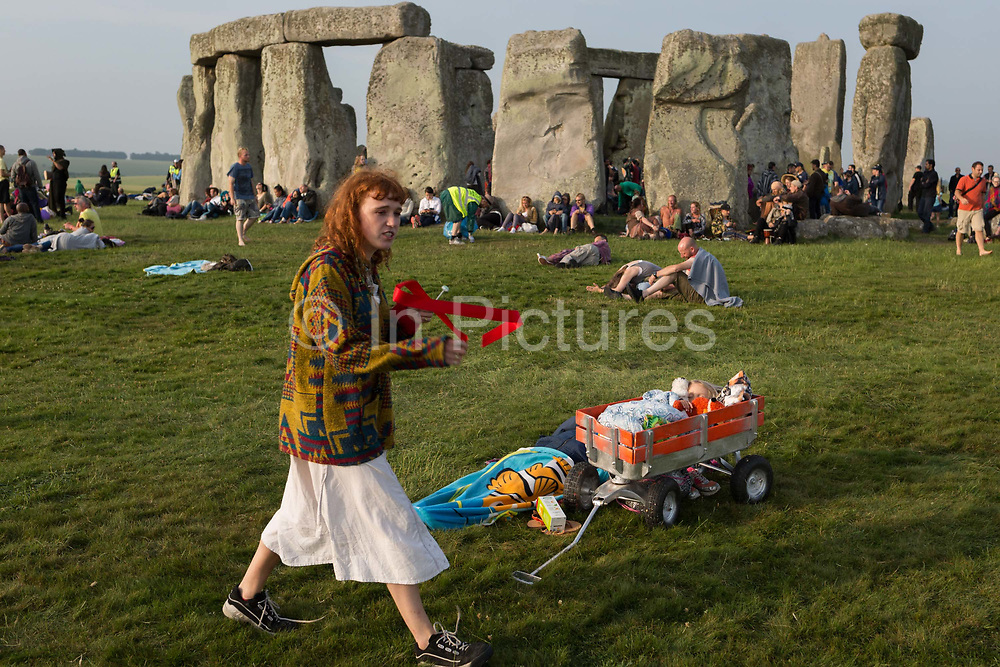 Spiritual revellers celebrate the summer Solstice mid-summer and longest day at the ancient stones of Stonehenge, on 21st June 2017, in Wiltshire, England. According to pagans, the Stonehenge is a sacred place that links the Earth, Moon, Sun and the seasons. Built in three phases between 3,000 B.C. and 1,600 B.C. its purpose remains under study. However, it's known that if you stand in just the right place inside the monument on summer solstice, through the entrance towards a rough hewn stone outside the circle you will see the sun rise above the Heel Stone.