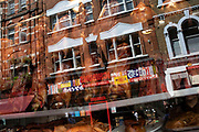 Chinese restaurant window reflecting nearby shops and buidings as crispy Peking Ducks hang in the window in Chinatown, London, United Kingdom. These ducks have been covered in spices and deep fried to give them a glistening and crispy skin, a speciality of Chinese cooking. The present Chinatown is in the Soho area occupying the area in and around Gerrard Street. It contains a number of Chinese restaurants, bakeries, supermarkets, souvenir shops, and other Chinese-run businesses and is in itself a major tourist destination.