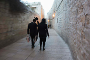 A man and women walk along a street in the Old City of Jerusalem on 30th March 2016 in Jerusalem, West Bank.