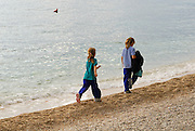 Two children (5 years old, 9 years old) striding along beach in late afternoon sunlight. Makarska, Croatia
