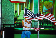 NEW YORK, NY: A man waving American flags walks through Times Square in Manhattan, New York, Sept 22, 2001. A wave of patriotism swept New York and the US after terrorists crashed two hijacked jetliners into the World Trade Center collapsing the towers on Sept 11, 2001, killing more 2,900 people.   PHOTO BY JACK KURTZ