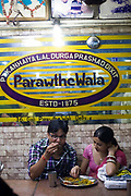 Customers eating paratha inside Parawthe Wala restaurant in Old Delhi, India<br /> Gali Paranthe Wali or Paranthe wali Gali means the the street of fried bread and name of a narrow street in Chandni Chowk Old Delhi, noted for its series of shops selling paratha. The parantha is an Indian fried bread, folded and filled with fillings and then fried