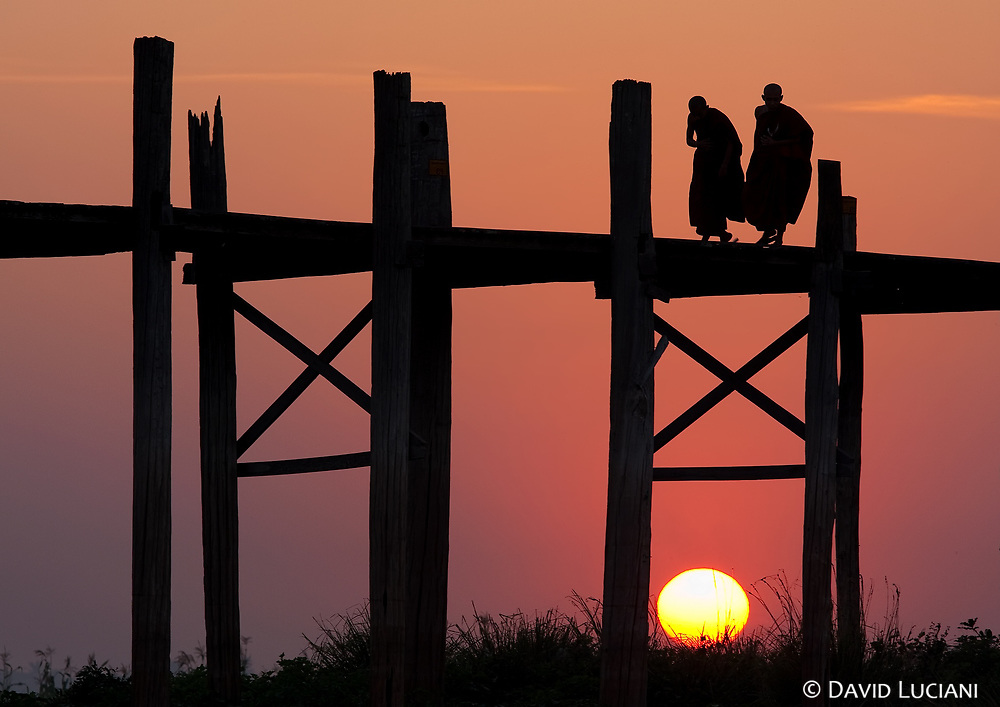 Two monks crossing the bridge while a magnificient sunset atmosphere surrounds the whole area. The best time for visiting the U Bein Bridge is early in the morning or late in the evening.